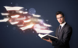 Young guy reading a book with flying sheets coming out of the bo. Ok, magical reading concept Stock Photos