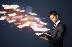 Young guy reading a book with flying sheets coming out of the bo Royalty Free Stock Photos