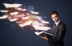 Young guy reading a book with flying sheets coming out of the bo Stock Photos