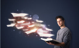 Young guy reading a book with flying sheets coming out of the bo. Ok, magical reading concept Royalty Free Stock Photo