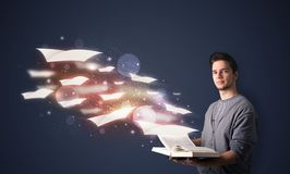 Young guy reading a book with flying sheets coming out of the bo Stock Images