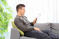 Young guy reading something on a tablet at home Royalty Free Stock Photo