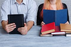 A guy reads an e-book, and a girl reads a variety of different other books. Learning concept. Royalty Free Stock Photos