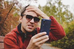 Young guy reads news or SMS on a mobile phone and holds his head with his hand. disappointment of the message on the royalty free stock images
