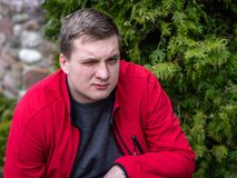 A young guy in a red jacket smokes an electronic cigarette stock photos