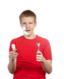 The young guy in a red t-shirt with the razor and a small brush in hands Royalty Free Stock Photos