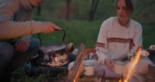 A young guy removes a teapot from stones and pours water into a mug for his girlfriend. A young couple is resting in nature stock video