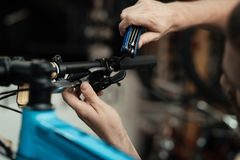 A young guy repairs a bicycle. Royalty Free Stock Photography