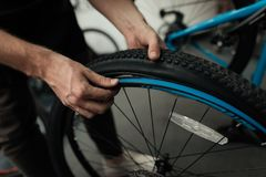A young guy repairs a bicycle. Stock Photo
