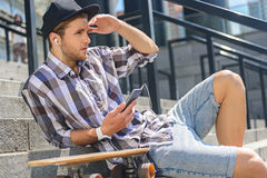 Young guy resting near skate on staircase. Male skater is sitting on stairs and relaxing. He is listening to music from smartphone. Man is covering face from Stock Image