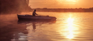 A young guy rides a boat on a lake during a golden sunset. Image of silhouette, Rower at sunset. Man rowing a boat in backlight of Stock Photo