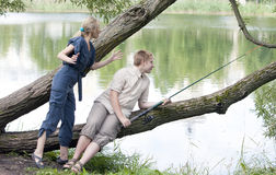 The young guy with a rod and the girl shows the size of fish Stock Photos