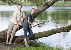 The young guy with a rod and the girl shows the size of fish Royalty Free Stock Images