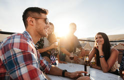 Young guy at rooftop party with best friends. Handsome young guy having a rooftop party with best friends. Group of people having good times together Royalty Free Stock Photo