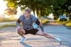 A young guy runner in the early morning makes gymnastics of his feet in headphones. A warm-up of the joints of the Royalty Free Stock Photos