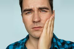 Portrait of a man in painful expression with a toothache. A young guy with a sad emotion on her face holding his hand over the patient`s jaw on a blue royalty free stock image