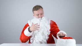 A young guy in Santa Claus costume takes off his hat 50 fps. 4k stock video footage