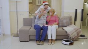Young guy in Santa`s hat hugs grandparents, happy family shows thumbs up. Elderly people hugs and sits on couch in living room at home. Senior man talks with his stock video footage
