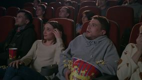 Young guy scared while watching horror film in movie theatre