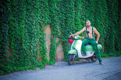 Young guy on a scooter against a wall of plants Royalty Free Stock Photos