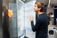 Young guy selecting domestic refrigerator Royalty Free Stock Photos