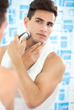 Young guy shaving his beard off with an electric shaver Royalty Free Stock Image
