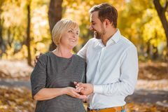 The guy hugs and holds his hand mom in the autumn park. A young guy in a shirt hugs and holds a hand mom smiling in a dress in an autumn park Stock Photos