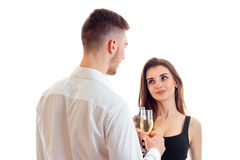 A young guy in a shirt looks at his girl and keeps wine glasses with her isolated on a white background Royalty Free Stock Photography