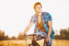 A young guy in a shirt and naked torso sits on a bicycle in headphones and listens to music outdoors, nature, field outside city Royalty Free Stock Photo