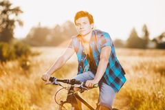 A young guy in a shirt and naked torso sits on a bicycle in headphones and listens to music outdoors, nature, field outside city Royalty Free Stock Photography