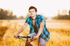 A young guy in a shirt and naked torso sits on a bicycle in headphones and listens to music outdoors, nature, field outside city Royalty Free Stock Image