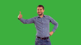 Young guy showing copy space on a green background with alpha channel stock video footage