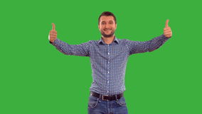 Young guy showing copy space on a green background with alpha channel stock footage
