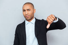 Young guy showing thumbs down sign over gray background Royalty Free Stock Photo