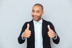 Young guy showing thumbs up sign over gray background Royalty Free Stock Images