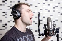 A young guy singer and rock musician sings in a studio condenser microphone in headphones in a recording studio. Record voice to microphone. Vocal is a rock Stock Image