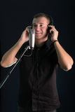 Young guy singing in the studio microphone. On dark background Royalty Free Stock Image