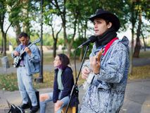 Young guy sings songs and plays guitar on a jeans jacket in a park on a natural background. Music concept. An excellent young men with a black hat plays the stock photos