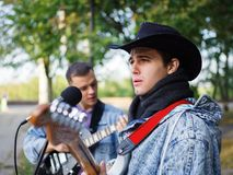 Young guy sings songs and plays guitar on a jeans jacket in a park on a natural background. Music concept. An excellent young men with a black hat plays the stock photo