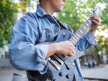 Young guy sings songs and plays guitar on a jeans jacket in a park on a natural background. Music concept. Handsome young man plays the guitar and sings songs stock image