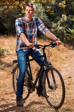 The young guy sits on bicycle. Stock Photography