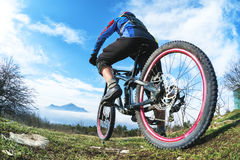 A young guy sits on a mountain bike atop a mountain, when below the mountains low clouds and fog Stock Image