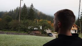 A young guy sits on a swing and looks at the forest in the fog stock footage