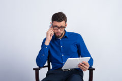 A young guy sits with tablet and phone Stock Photo