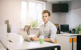 The young guy is sitting at the computer in the office with the windows behind his back. A young programmer is looking at the camera. The young guy is sitting at Stock Images