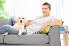 Young guy sitting on couch with a puppy at home royalty free stock photos