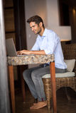 Young guy sitting at home and using laptop computer Royalty Free Stock Photo