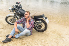Young guy sitting next to his vintage motorcycle Stock Photography