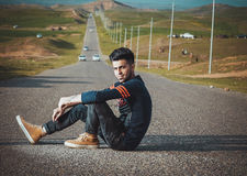 Young guy sitting on road Stock Photography
