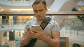 Young guy sitting in shopping mall cafe using smartphone, browsing, reading news, chatting friends. Young handsome guy in grey t-shirt sitting in food court cafe stock footage